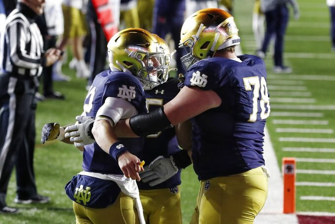 Notre Dame quarterback Ian Book, left, celebrates his touchdown with offensive lineman Tommy Kraemer (78) during the second half of an NCAA college football game against Boston College, Saturday, Nov. 14, 2020, in Boston. (AP Photo/Michael Dwyer)