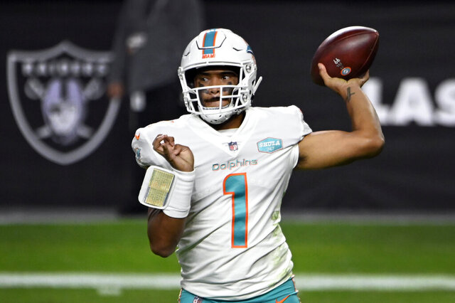 Miami Dolphins quarterback Tua Tagovailoa (1) looks to pass against the Las Vegas Raiders during an NFL football game, Sunday, Dec. 26, 2020, in Las Vegas. The Miami Dolphins need a good game Sunday to ensure they get to keep playing, and that's especially true for Tua Tagovailoa. Coach Brian Flores has benched Tagovailoa twice in the fourth quarter, including last week at Las Vegas, when backup quarterback Ryan Fitzpatrick helped Miami overcome a pair of deficits in the final 10 minutes. (AP Photo/David Becker)