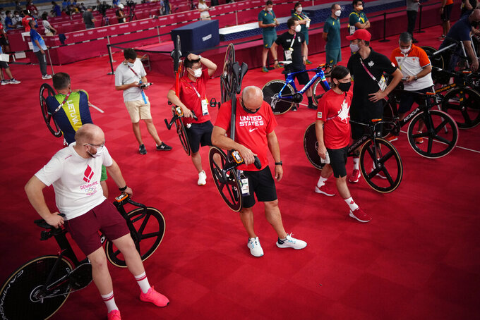 Team support staffs prepare for the track cycling men's keirin race at the 2020 Summer Olympics, Sunday, Aug. 8, 2021, in Izu, Japan. (AP Photo/Christophe Ena)