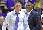 In this photo taken Feb. 23, 2019, LSU head coach Will Wade, left, and assistant coach Tony Benford, right, watch the second half of an NCAA college basketball game in Baton Rouge, La. Benford has been named interim head coach after Wade was suspended amid concerns about the recruiting tactics he used to build his team. (AP Photo/Bill Feig)