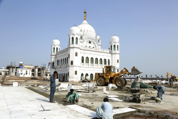 Pakistani workers give finishing touches to the shrine of Sikh spiritual leader Guru Nanak Dev, in Kartarpur, Pakistan, Monday, Sept. 16, 2019. Pakistani officials said Monday that a much-awaited visa-free border crossing for Sikh pilgrims from India will be ready by early November, allowing thousands of pilgrims to easily visit the Sikh shrine just inside Pakistan each day. (AP Photo/K.M. Chaudary)