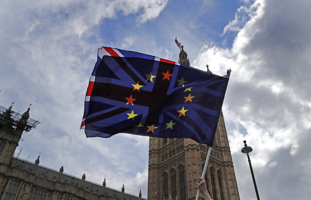 FILE - In this Thursday, April 4, 2019 file photo, a pro EU protestor waves flags opposite the House of Parliament in London. _ Anxious, angry, abandoned. Brexit elicits strong emotions, and as Britain's departure from the European Union approaches, more than 3 million U.K. residents who are citizens of EU countries feel the impending separation more strongly than most. (AP Photo/Frank Augstein, File)