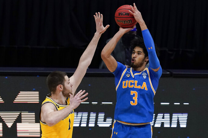 UCLA guard Johnny Juzang (3) shoots over Michigan center Hunter Dickinson (1) during the first half of an Elite 8 game in the NCAA men's college basketball tournament at Lucas Oil Stadium, Tuesday, March 30, 2021, in Indianapolis. (AP Photo/Michael Conroy)