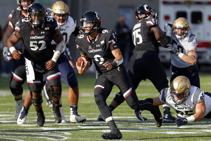 Cincinnati quarterback Desmond Ridder (9) breaks away from Navy defensive end Anthony Villalobos (95) in the first half of an NCAA college football game, Saturday, Nov. 3, 2018, in Cincinnati. (AP Photo/John Minchillo)