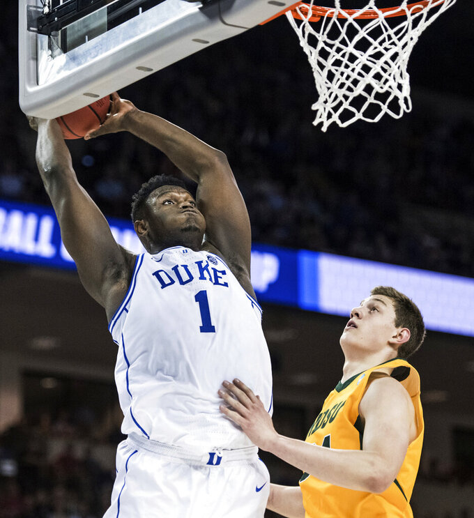 Duke forward Zion Williamson (1) goes up for a dunk against North Dakota State forward Rocky Kreuser (34) during the first half of a first-round game in the NCAA men's college basketball tournament Friday, March 22, 2019, in Columbia, S.C. (AP Photo/Sean Rayford)