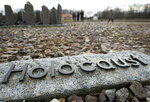 FILE - In this Monday, Jan. 27, 2020 file photo people walk behind the writing 'Holocaust' during the international Holocaust remembrance day in the former the Nazi concentration camp Buchenwald near Weimar, Germany. Friedrich Karl Berger, a 95-year-old former Nazi concentration camp guard, was deported to his native Germany on orders from a Tennessee court. Berger has agreed to be questioned by German prosecutors as they re-examine whether there is enough evidence against him to bring charges, authorities said Monday. (AP Photo/Jens Meyer, file)