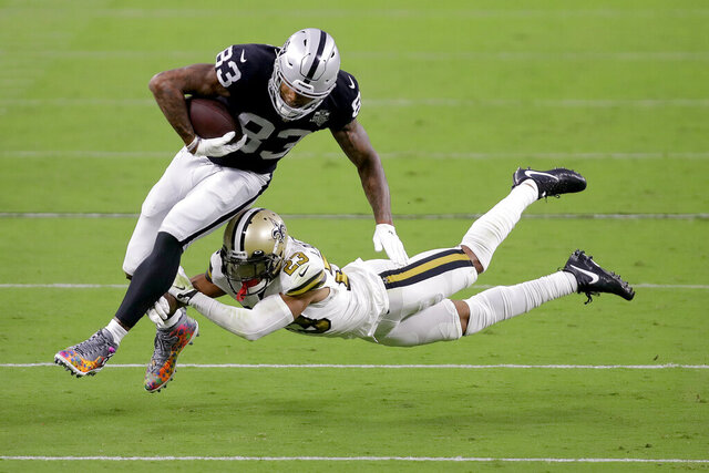 New Orleans Saints cornerback Marshon Lattimore (23) tackles Las Vegas Raiders tight end Darren Waller (83) during the first half of an NFL football game, Monday, Sept. 21, 2020, in Las Vegas. (AP Photo/Isaac Brekken)
