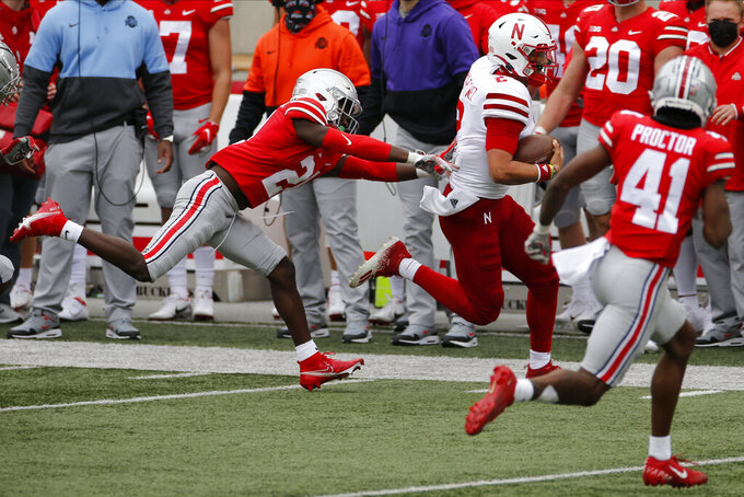 Ohio State defensive back Marcus Williamson, left, chases Nebraska quarterback Adrian Martinez during the second half of an NCAA college football game Saturday, Oct. 24, 2020, in Columbus, Ohio.  (AP Photo/Jay LaPrete)
