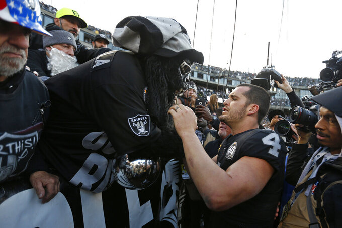 "Oakland Raiders quarterback Derek Carr (4) is met by Gorilla Nilla in ""The Black Hole"" at the end of an NFL football game against the Jacksonville Jaguars in Oakland, Calif., Sunday, Dec. 15, 2019. (AP Photo/D. Ross Cameron)"