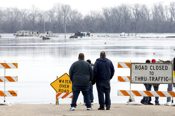 FILE - In this March 17, 2019 file photo, people stand at the edge of a flooded road in Plattsmouth, Neb. Although President Donald Trump has expressed doubt about climate change, even calling it a hoax, a National Climate Assessment released last year by the White House warned that natural disasters in the U.S. are worsening because of global warming. (AP Photo/Nati Harnik)