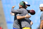 Buffalo Bills quarterback Josh Allen, with football, embraces Green Bay Packers quarterback Aaron Rodgers as they warm up prior to the start of the first half of a preseason NFL football game, Saturday, Aug. 28, 2021, in Orchard Park, N.Y. (AP Photo/Joshua Bessex)