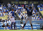 San Diego Padres' Fernando Tatis Jr., right, gestures as he scores after hitting a three-run home run as Los Angeles Dodgers catcher Austin Barnes stands at the plate during the fifth inning of a baseball game Sunday, July 7, 2019, in Los Angeles. (AP Photo/Mark J. Terrill)