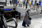 A nun wearing a face mask to prevent the spread of coronavirus climbs stairs of a subway in downtown Madrid, Spain, Friday, Sept. 18, 2020. With more than 11,000 new daily coronavirus cases, the attention in Spain is focusing on its capital, where officials are mulling localized lockdowns and other measures to bring down the curve of contagion. (AP Photo/Manu Fernandez)