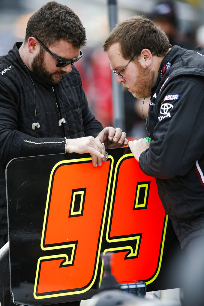 Members of Tommy Joe Martins' pit crew prepare their pit box sign before a NASCAR auto race at Texas Motor Speedway, Saturday, March 30, 2019, in Fort Worth, Texas. (AP Photo/Brandon Wade)