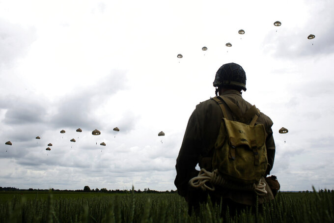 FILE - In this Wednesday, June 5, 2019 file photo, a WWII enthusiast watches French and British parachutists jumping during a commemorative parachute jump over Sannerville, Normandy, France. In sharp contrast to the 75th anniversary of D-Day, this year's 76th will be one of the loneliest remembrances ever, as the coronavirus pandemic is keeping nearly everyone from traveling. (AP Photo/Thibault Camus, File)