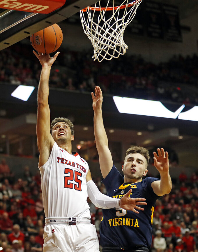 Texas Tech's Davide Moretti (25) lays up the ball around West Virginia's Jordan McCabe (5) during the first half of an NCAA college basketball game Monday, Feb. 4, 2019, in Lubbock, Texas. (AP Photo/Brad Tollefson)