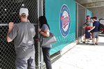Baseball fans look through a fence at Hammond Stadium after the cancellation of a game between the Minnesota Twins and the Baltimore Orioles, Thursday, March 12, 2020, in Fort Myers, Fla. Major League Baseball has suspended the rest of its spring training game schedule because if the coronavirus outbreak. MLB is also delaying the start of its regular season by at least two weeks. (AP Photo/Elise Amendola)