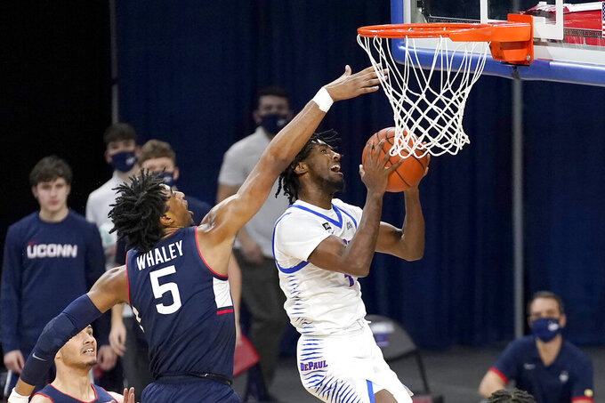 DePaul's Javon Freeman-Liberty, right, drives past Connecticut's Isaiah Whaley during the first half of an NCAA college basketball game Monday, Jan. 11, 2021, in Chicago. (AP Photo/Charles Rex Arbogast)