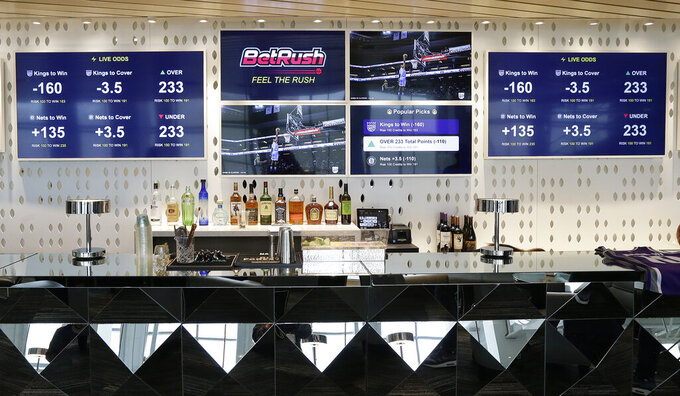 FILE - In this March 19, 2019, file photo, video screens display the types of bets that can be placed at the Golden 1 Center's Skyloft Predictive Gaming Lounge, in Sacramento, Calif. Professional sports leagues have found a way to cash in by selling their official data to gambling companies, making the case that the leagues are creating new products for gamblers to bet on. (AP Photo/Rich Pedroncelli, File)