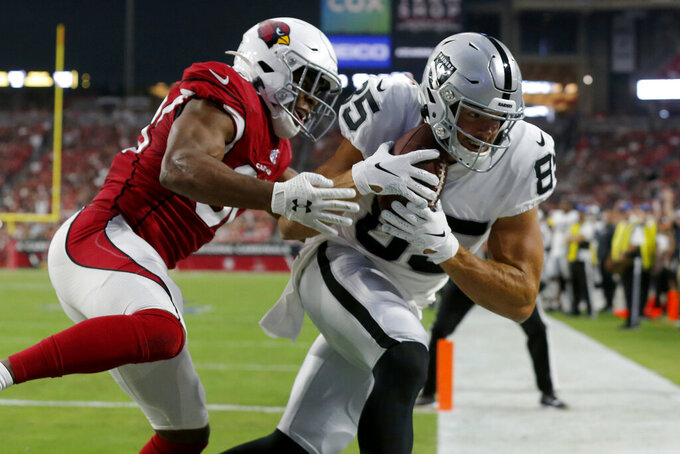 Oakland Raiders tight end Derek Carrier (85) scores a touchdown as Arizona Cardinals defensive back Rudy Ford defends during the first half of an an NFL football game, Thursday, Aug. 15, 2019, in Glendale, Ariz. (AP Photo/Rick Scuteri)