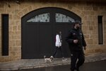A private security guard stands nearby as a woman walks her dog past the house of ex-Nissan chief Carlos Ghosn in Beirut, Lebanon, Friday, Jan. 3, 2020. The former Nissan Motor Co. Chairman fled Japan this week while awaiting trial on financial misconduct charges and appeared in Lebanon. (AP Photo/Maya Alleruzzo)