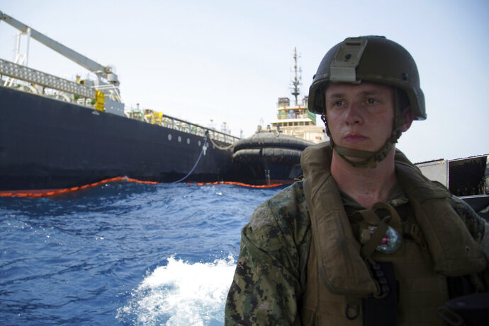The damaged Panama-flagged, Japanese owned oil tanker Kokuka Courageous, that the U.S. Navy says was damaged by a limpet mine, is seen behind a U.S. sailor, during a trip organized by the Navy for journalists, off Fujairah, United Arab Emirates, Wednesday, June 19, 2019. The limpet mines used to attack the oil tanker near the Strait of Hormuz bore