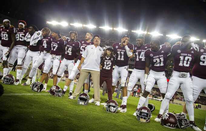 Texas A&M coach Jimbo Fisher lines up with his son Trey (12) and the Texas A&M football team to sing the Aggie War Hymn after a 59-7 win over Northwestern State in an NCAA college football game Thursday, Aug. 30, 2018, in College Station, Texas. (AP Photo/Sam Craft)