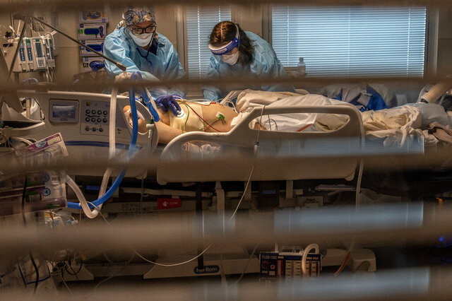 Phlebotomist lab assistant Jennifer Cukati, right, and Registered Nurse Carina Klescewski, left, care for a COVID-19 patient inside the Sutter Roseville Medical Center ICU in Roseville, Calif., on Tuesday, Dec. 22, 2020. The patient came in the night before