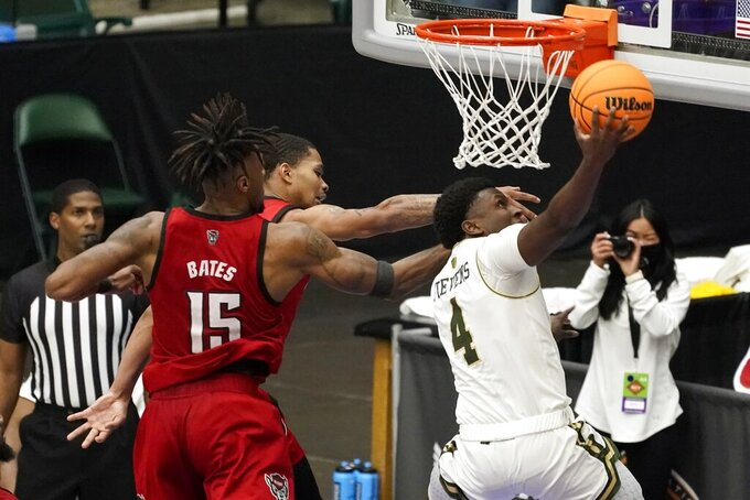 Colorado State guard Isaiah Stevens (4) goes up for a shot after getting past the defense of North Carolina State's Manny Bates (15) and Shakeel Moore, left rear, during the second half of an NCAA college basketball game in the quarterfinals of the NIT, Thursday, March 25, 2021, in Frisco, Texas. (AP Photo/Tony Gutierrez)