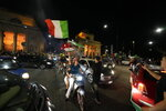 Italy's fans celebrate in Milan, Italy, Monday, July 12, 2021, after Italy beat England to win the Euro 2020 soccer championships in a final played at Wembley stadium in London. Italy beat England 3-2 in a penalty shootout after a 1-1 draw. (AP Photo/Luca Bruno)
