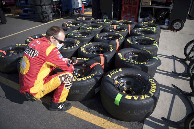 Pit member for Kyle Busch (18) checks tires before a NASCAR Cup Series auto race at the Martinsville Speedway in Martinsville, Va., Sunday, Nov.1, 2020. (AP Photo/Lee Luther Jr.)