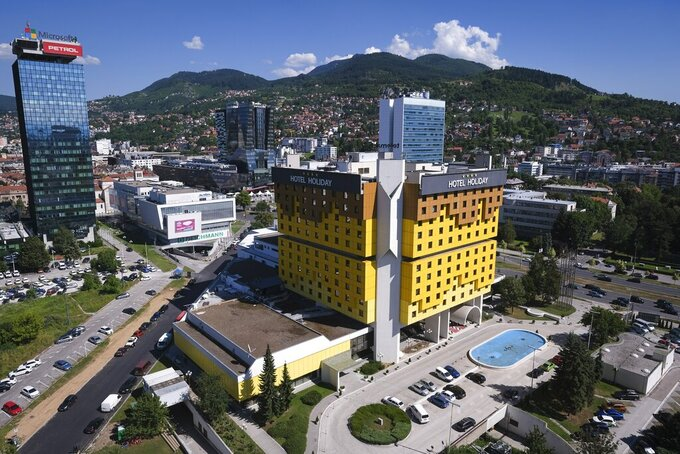 The Holiday Hotel, which opened as Holiday Inn, a luxurious accommodation for world's royalty, film stars and other dignitaries who came to watch the 1984 Winter Olympics, and less than a decade later, became ground zero of the bloody siege of Sarajevo in the 1990's, photographed from a nearby building, in Sarajevo, Bosnia, Wednesday, July 29, 2020. The bright yellow Holiday Hotel in downtown Sarajevo, a famous symbol of survival of the Bosnian capital, has seen good and bad times in its turbulent history, but now the landmark's survival is in more danger than ever, with the coronavirus pandemic leaving it with only a few occasional guests. (AP Photo/Kemal Softic)