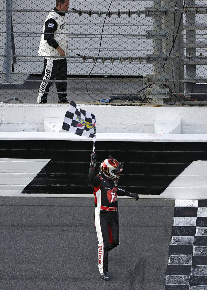 Michael Annett waves the checkered flag after getting it from a race official at the end of the NASCAR Xfinity auto race Saturday, Feb. 16, 2019, at Daytona International Speedway in Daytona Beach, Fla. Annett won the race. (AP Photo/Chris O'Meara)
