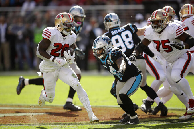 San Francisco 49ers running back Tevin Coleman runs with the ball for a touchdown past Carolina Panthers outside linebacker Shaq Thompson during the first half of an NFL football game in Santa Clara, Calif., Sunday, Oct. 27, 2019. The touchdown was Coleman's third of the first half. (AP Photo/Ben Margot)