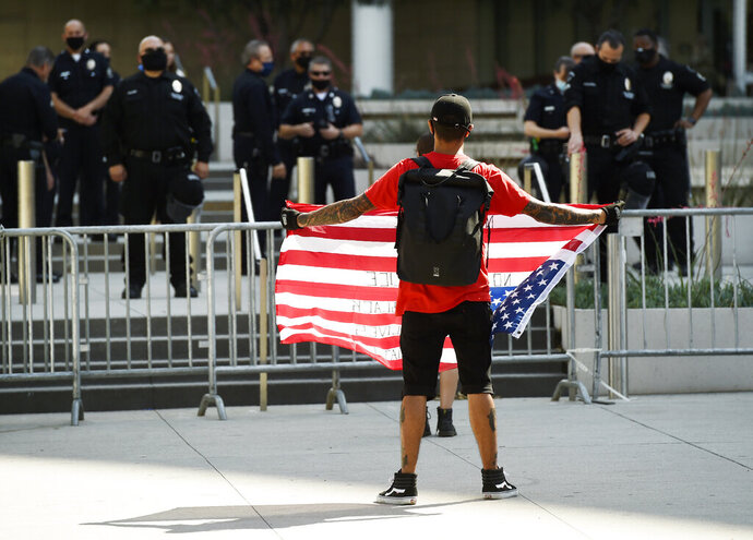 Stephen Chang of Los Angeles protests in front of police officers at Los Angeles Police Department headquarters, Thursday, June 4, 2020, in Los Angeles. Protests continue to be held in U.S. cities over the death of George Floyd, a black man who died after being restrained by Minneapolis police officers on May 25. (AP Photo/Chris Pizzello)