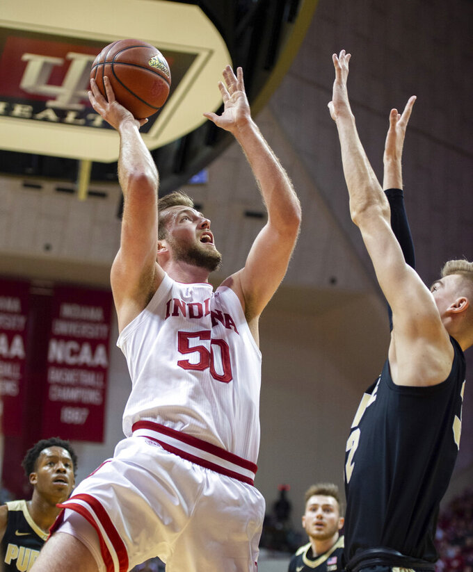 Indiana forward Joey Brunk (50) takes a shot as Purdue center Matt Haarms (32) defends during the first half of an NCAA college basketball game, Saturday, Feb. 8, 2020, in Bloomington, Ind. (AP Photo/Doug McSchooler)