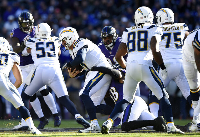 Los Angeles Chargers quarterback Philip Rivers, center, is sacked by Baltimore Ravens inside linebacker Patrick Onwuasor (48) in the first half of an NFL wild card playoff football game, Sunday, Jan. 6, 2019, in Baltimore. (AP Photo/Gail Burton)