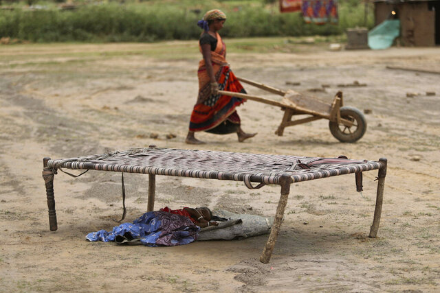 An Indian woman works at a brick kiln as her child sleeps under a cot during lockdown to curb the spread of new coronavirus on the outskirts of Jammu, India, Sunday, May 10, 2020. India's lockdown entered a sixth week on Sunday, though some restrictions have been eased for self-employed people unable to access government support to return to work. (AP Photo/Channi Anand)