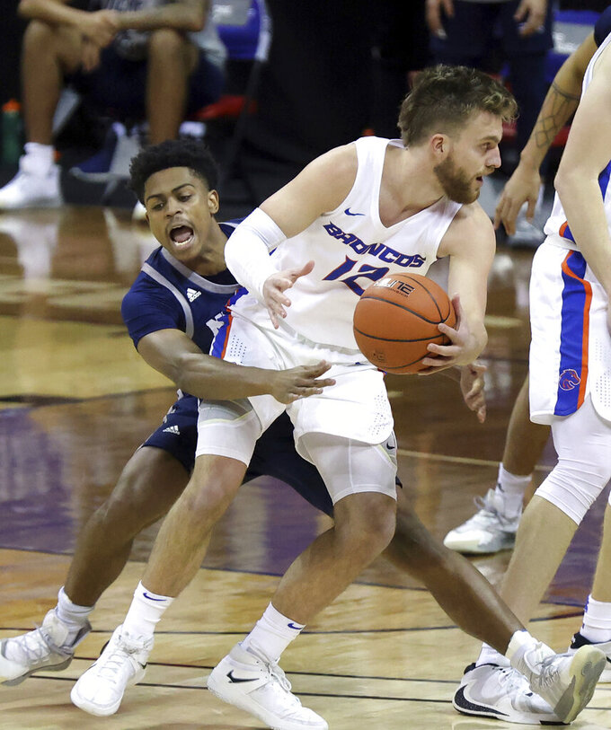 Nevada guard Grant Sherfield reaches for the ball as Boise State guard Max Rice (12) drives during the first half of an NCAA college basketball game in the quarterfinals of the Mountain West Conference men's tournament Thursday, March 11, 2021, in Las Vegas. (AP Photo/Isaac Brekken)