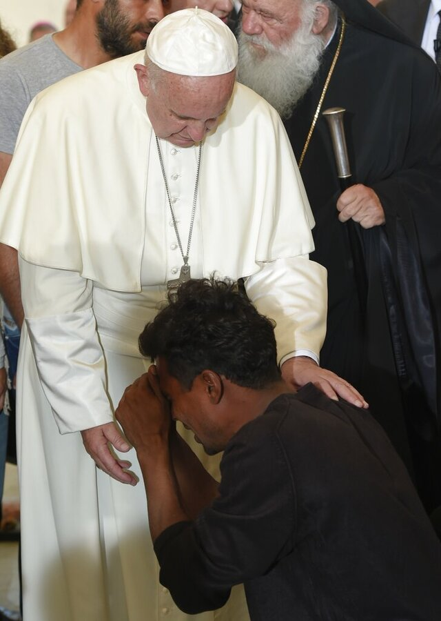 FILE - In this Saturday, April 16, 2016 file photo, Pope Francis blesses a man kneeling in front of him, at the Moria refugee camp, on the Greek island of Lesbos. Pope Francis expressed solidarity Sunday, Sept. 13, 2020, with the thousands of migrants who had been left homeless by the fires at a refugee camp in Lesbos, Greece, and called for a