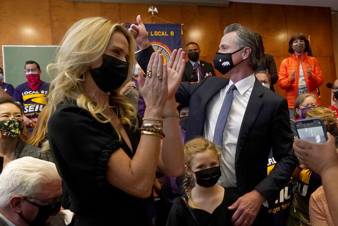 Gov. Gavin Newsom, middle right, gestures next to his wife, Jennifer Siebel Newsom, foreground, and their daughter, Brooklynn, bottom, after speaking to volunteers in San Francisco, Tuesday, Sept. 14, 2021. The recall election that could remove California Democratic Gov. Newsom is coming to an end. Voting concludes Tuesday in the rare, late-summer election that has emerged as a national battlefront on issues from COVID-19 restrictions to climate change. (AP Photo/Jeff Chiu)