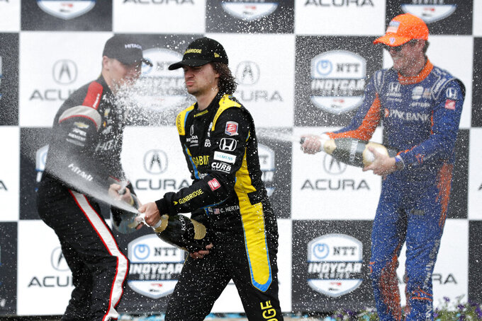 Colton Herta, center, sprays the crowd after winning the Grand Prix of Long Beach IndyCar auto race with second-place finisher Josef Newgarden, left, and third-place winner Scott Dixon, right, on Sunday, Sept. 26, 2021, in Long Beach, Calif. (AP Photo/Alex Gallardo)