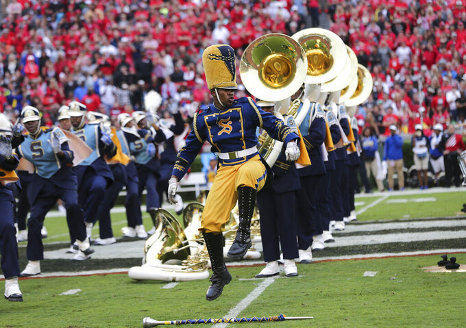 FILE - In this Sept. 26, 2015, file photo, Southern drum major Keith Morgan, of New Orleans, performs with the band during a halftime show an NCAA college football game against Georgia in Athens, Ga. HBCUs across the country earn some money from television contracts. But the primary source of revenue from football comes from putting fans in the stands. Programs could take a huge financial hit if fans are banned from football games this fall. (AP Photo/John Bazemore, File)