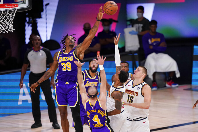 Los Angeles Lakers' Dwight Howard (39) reaches for the ball above a crowd of players including Denver Nuggets' Nikola Jokic (15) during the second half of an NBA conference final playoff basketball game Saturday, Sept. 26, 2020, in Lake Buena Vista, Fla. (AP Photo/Mark J. Terrill)