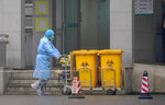 Staff move bio-waste containers past the entrance of the Wuhan Medical Treatment Center, where some infected with a new virus are being treated, in Wuhan, China, Wednesday, Jan. 22, 2020. The number of cases of a new coronavirus from Wuhan has risen over 400 in China Chinese health authorities said Wednesday. (AP Photo/Dake Kang)