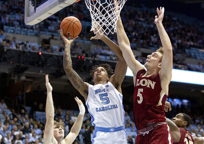 North Carolina's Armando Bacot, left, attempts a shot as Elon's Federico Poser, right, defends during the first half of an NCAA college basketball game in Chapel Hill, N.C., Wednesday, Nov. 20, 2019. (AP Photo/Ben McKeown)