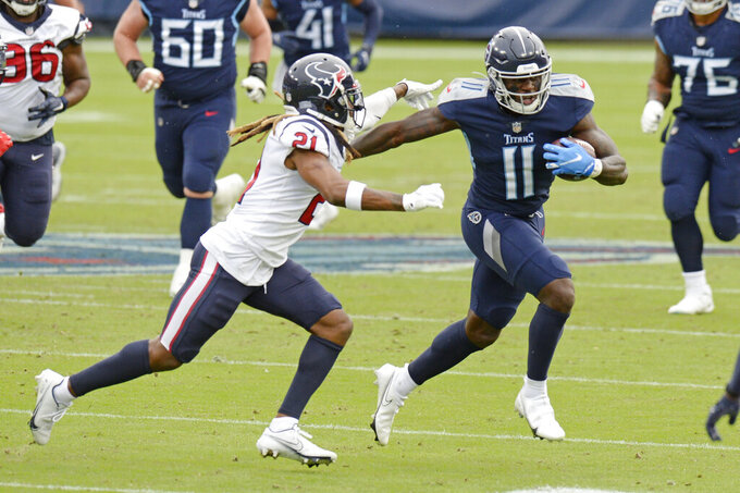 Tennessee Titans wide receiver A.J. Brown (11) is chased by Houston Texans cornerback Bradley Roby (21) in the first half of an NFL football game Sunday, Oct. 18, 2020, in Nashville, Tenn. (AP Photo/Mark Zaleski)