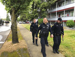Police leave the scene of a police shooting on Wednesday May 15, 2019 in Salem, Ore. after a suspect in the shooting of a policewoman was arrested. Around 100 officers from several departments assisted.(AP Photo/Andrew Selsky)