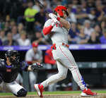 Philadelphia Phillies batter Bryce Harper, right, hits a three-run home run against the Colorado Rockies in the seventh inning of a baseball game in Denver, Saturday, April 20, 2019. Rockies catcher Drew Butera, left, reaches for the pitch. (AP Photo/Joe Mahoney)