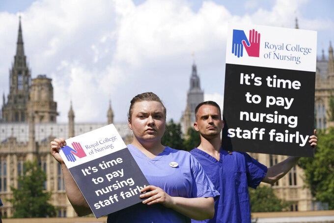 Nurses hold placards outside the Royal College of Nursing (RCN) in Victoria Tower Gardens, London, Wednesday July 21, 2021. In a statement Wednesday July 21, 2021, the British government has tripled its pay increase offer for more than a million National Health Service employees in England, but unions said the proposed boost was insufficient given an anticipated spike in inflation. (Jonathan Brady/PA via AP)